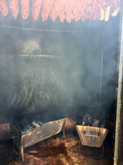 Troughs full of smoldering wood is used to smoke the meat.