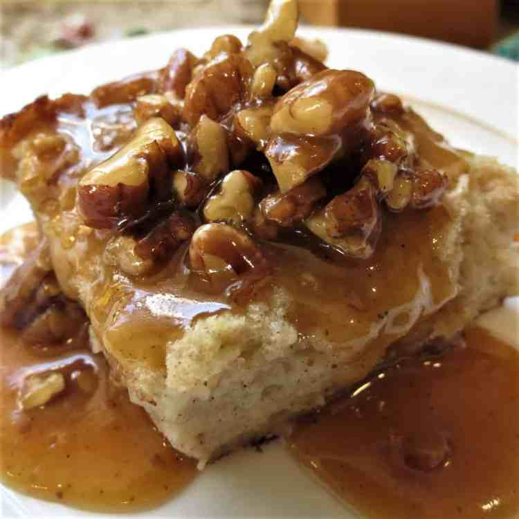 Bread Pudding topped with a Pumpkin Pecan Praline Sauce on white plate.
