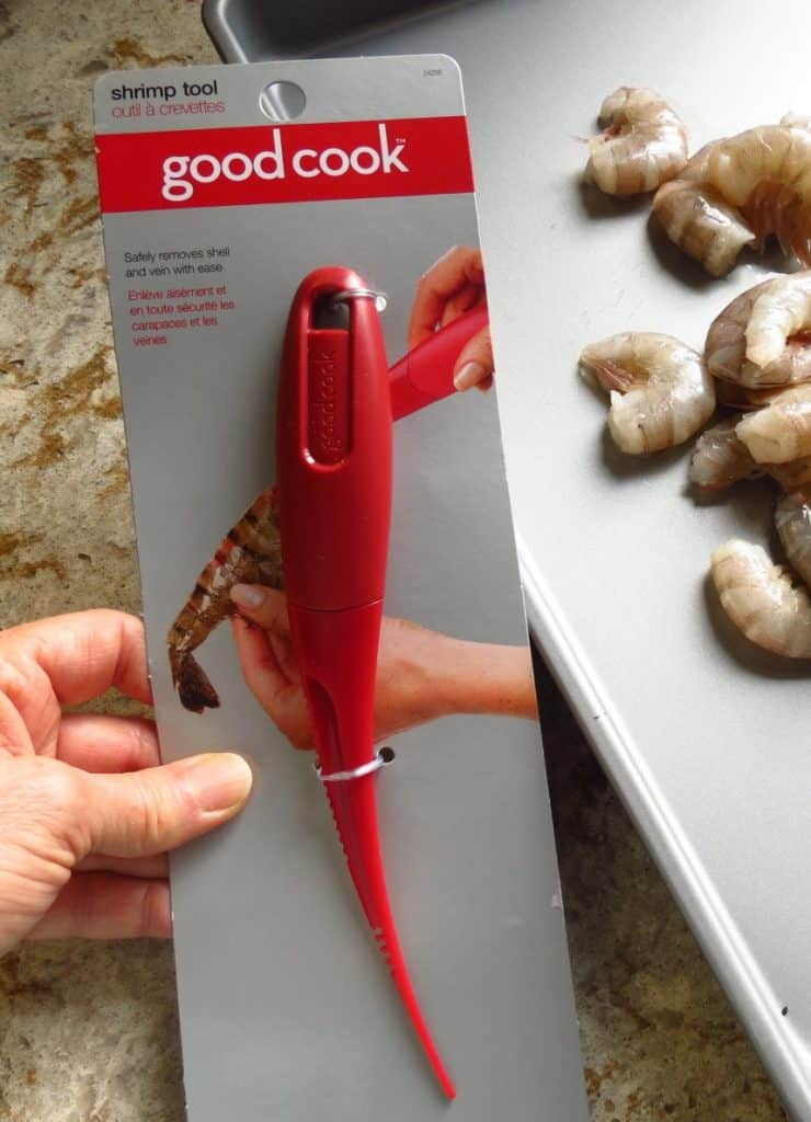 Close up of shrimp tool with unpeeled shrimp in background