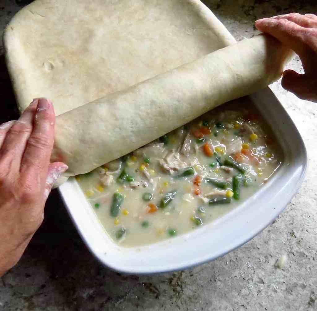 Rolling pie dough onto Chicken Pot Pie.