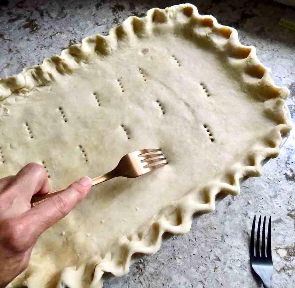 Fork Piercing top of dough for Chicken Pot Pie.