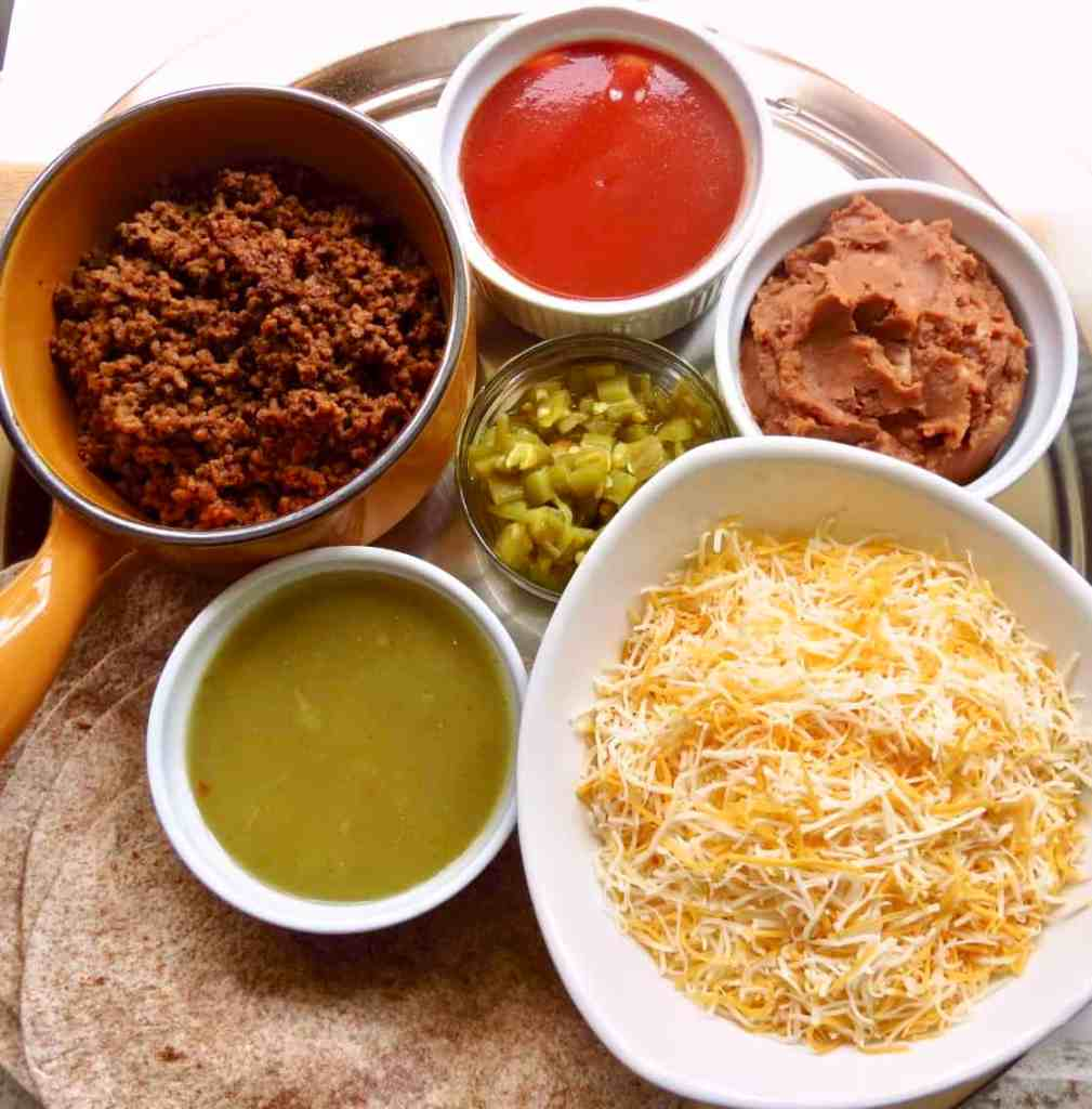 Ingredients of cheese, beef, refried beans, green chiles, and sauces for Easy Beef Enchiladas.