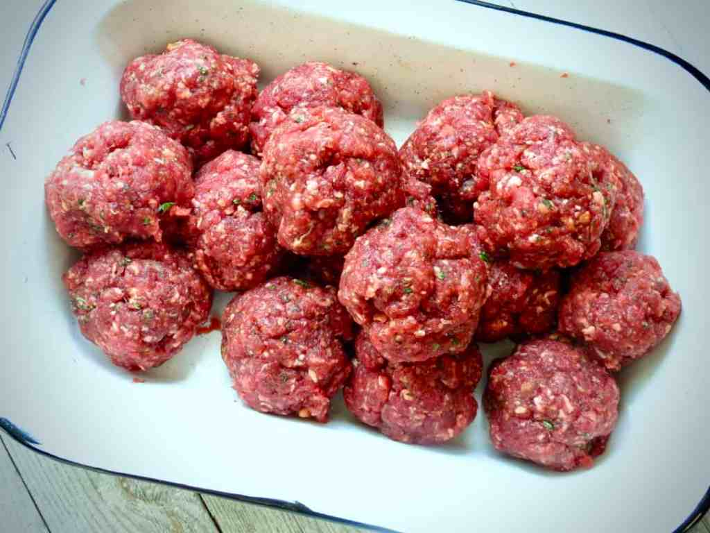 Rectangular dish of raw meatballs.