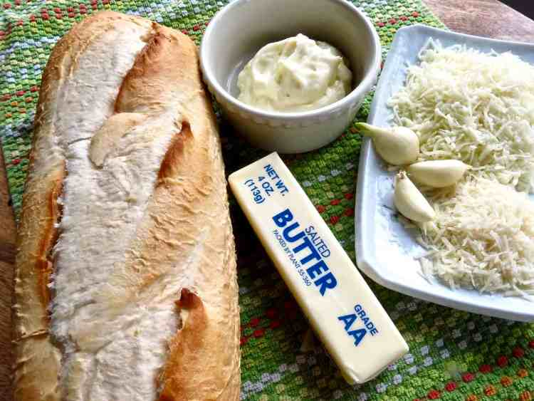 Ingredients of butter, mayonnaise in a bowl, garlic bulbs, and grated white cheeses on a green towel.