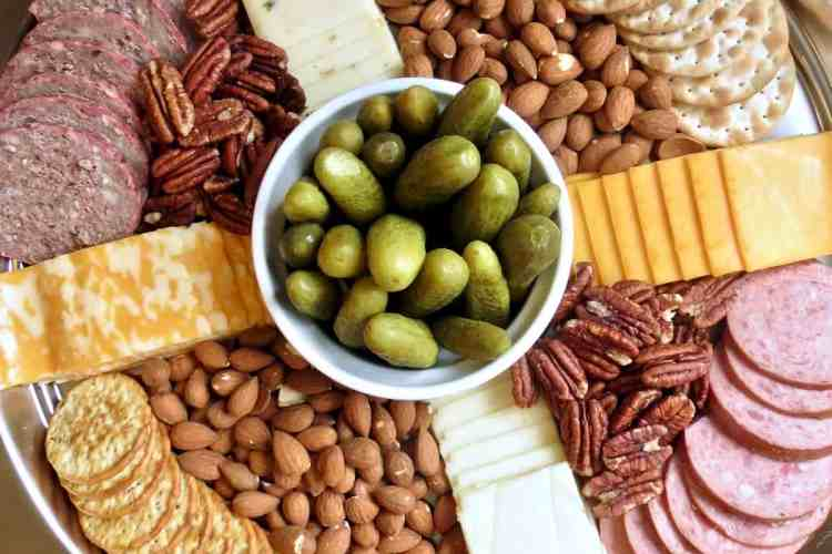 Sliced salami, summer sausage, nuts, sliced cheese, crackers arranged around a dish of pickles on a tray for Easy Appetizers To Tease And Appease The Appetite.