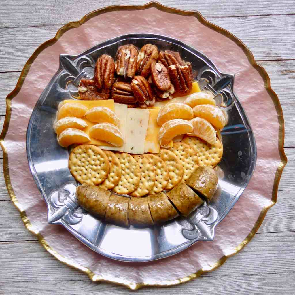 A silver plate with fleur de lis filled with boudin, crackers, cheeses, pecans, and orange slices for Easy Appetizers To Tease And Appease The Appetite.