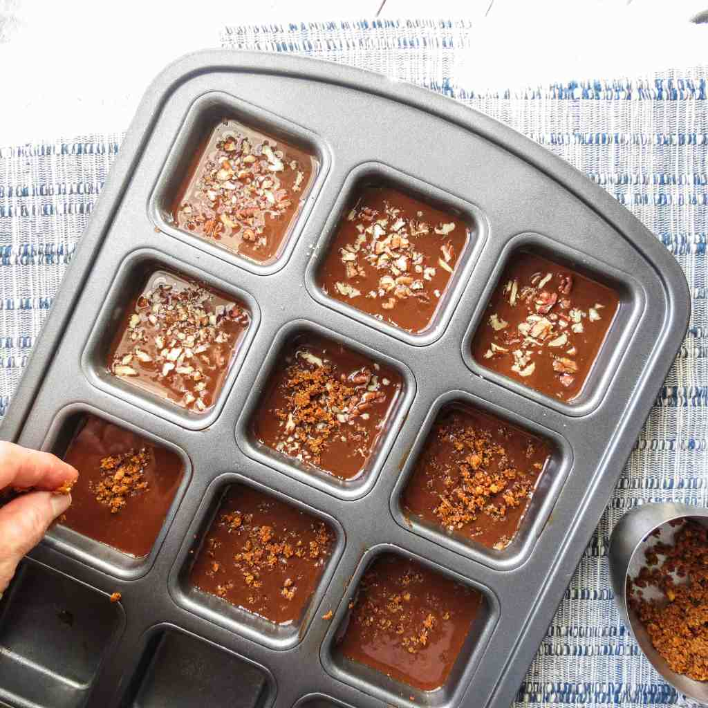A hand sprinkling Cajun cracklins and pecans onto Fat Bombs in square molds.