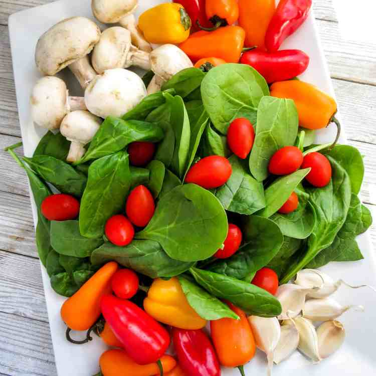 Fresh spinach, mushrooms, colored mini peppers, and grape tomatoes on a white tray.