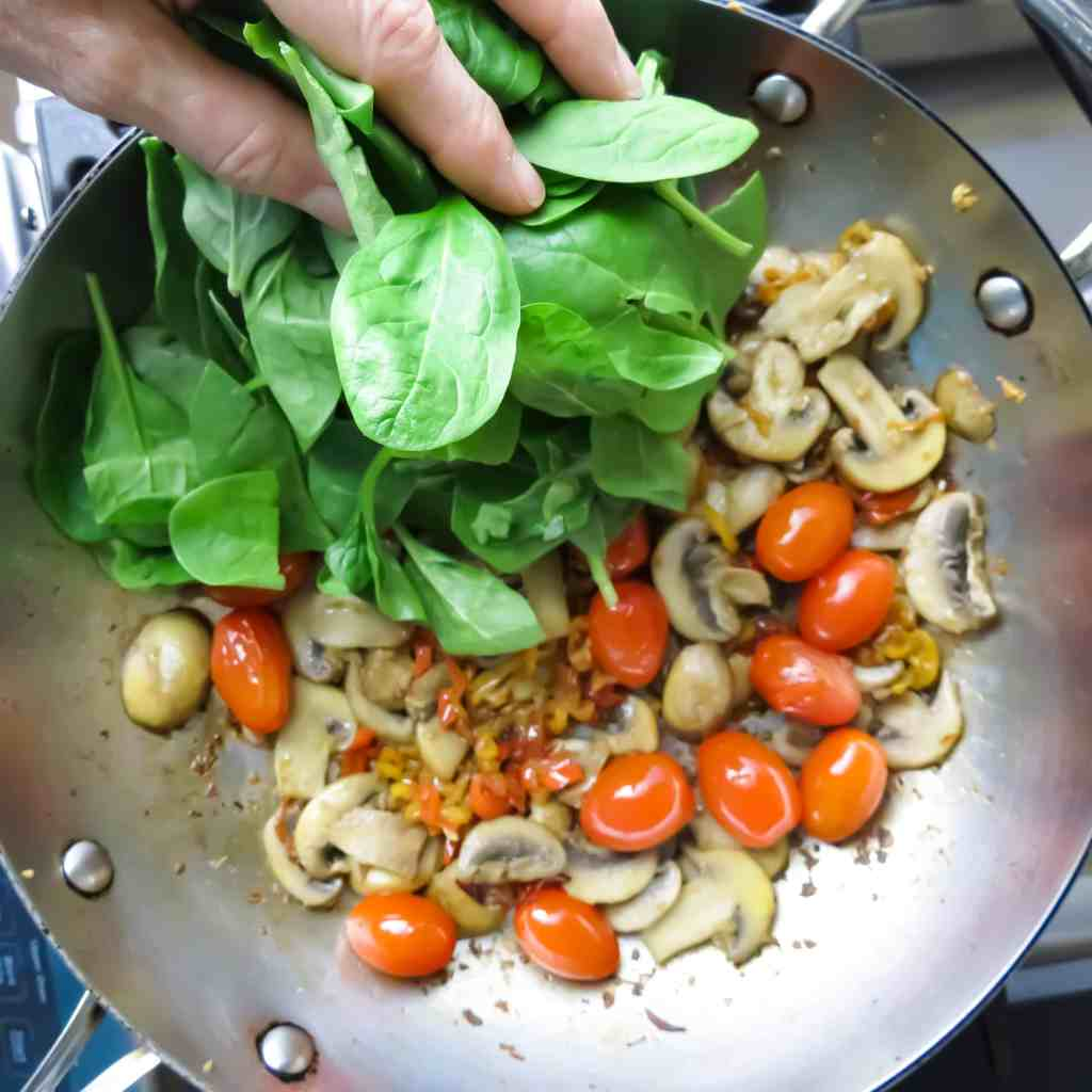 A handful of fresh green spinach thrown into a pan of sautéed peppers, mushrooms, and grape tomatoes with a wooden spoon for Spinach Medley, A Healthy Spinach Side Dish.