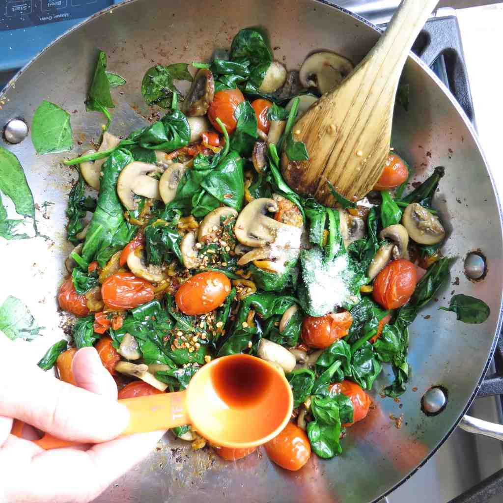 A Pan of sautéed spinach, peppers, mushrooms, and grape tomatoes with a wooden spoon for Spinach Medley, A Healthy Spinach Side Dish.