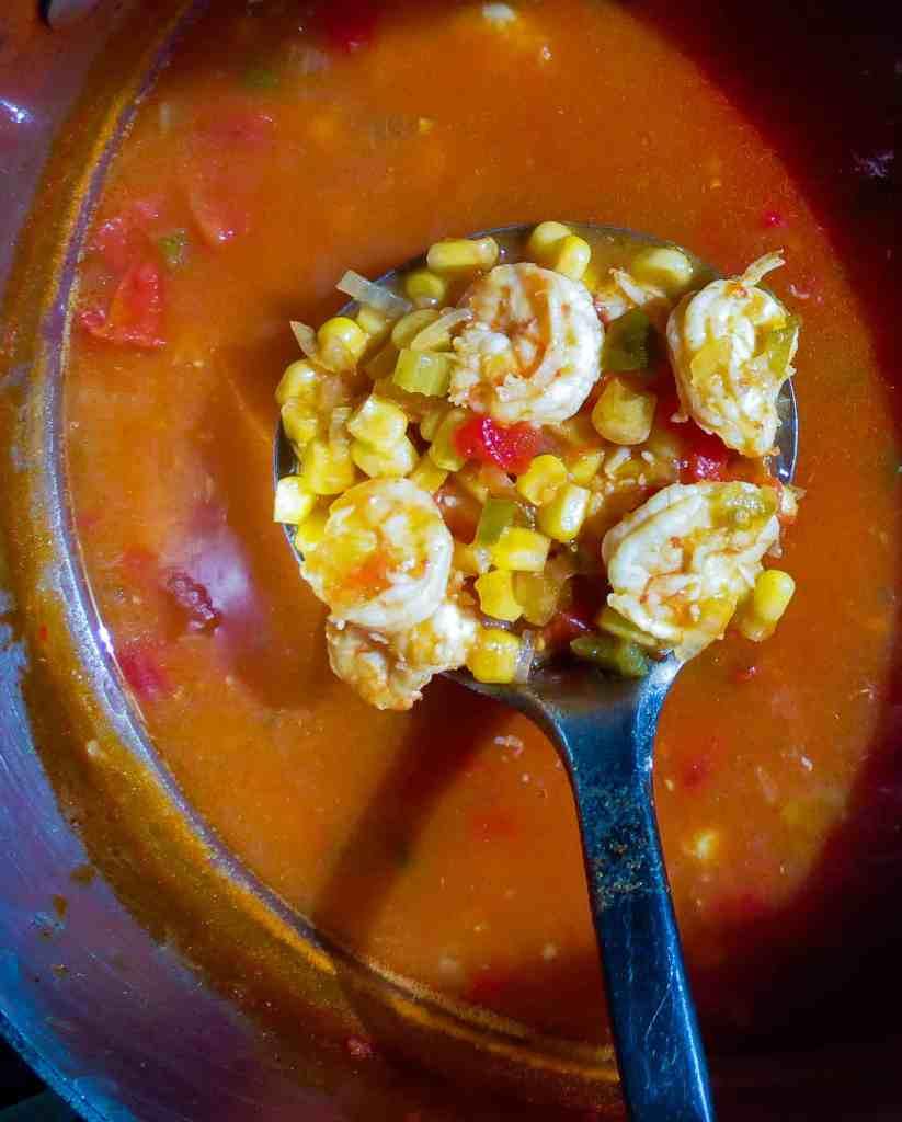 A pot of Shrimp And Corn Soup with a ladle stirring soup.
