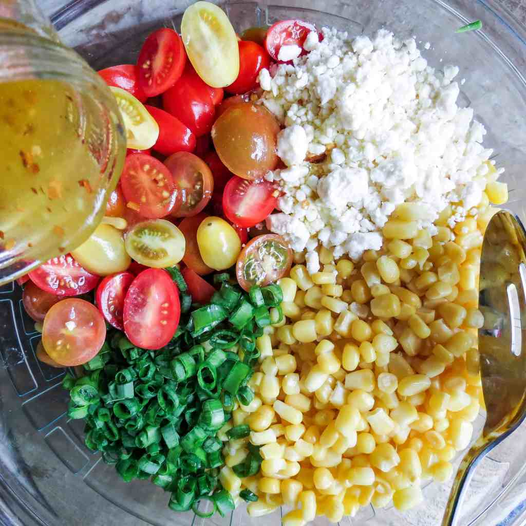 A glass bowl full of ingredients for Corn Salad With Tomatoes with a jar of vinaigrette being poured over it.