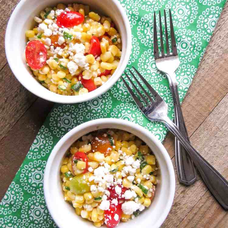 Two white bowls with each a serving of Corn Salad With Tomatoes on a green and white printed napkin with two forks.