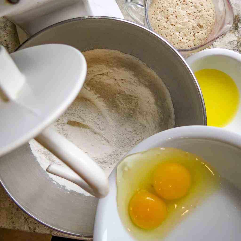 2 egg yolks being poured into flour mixture of Easy No-Knead Bread.