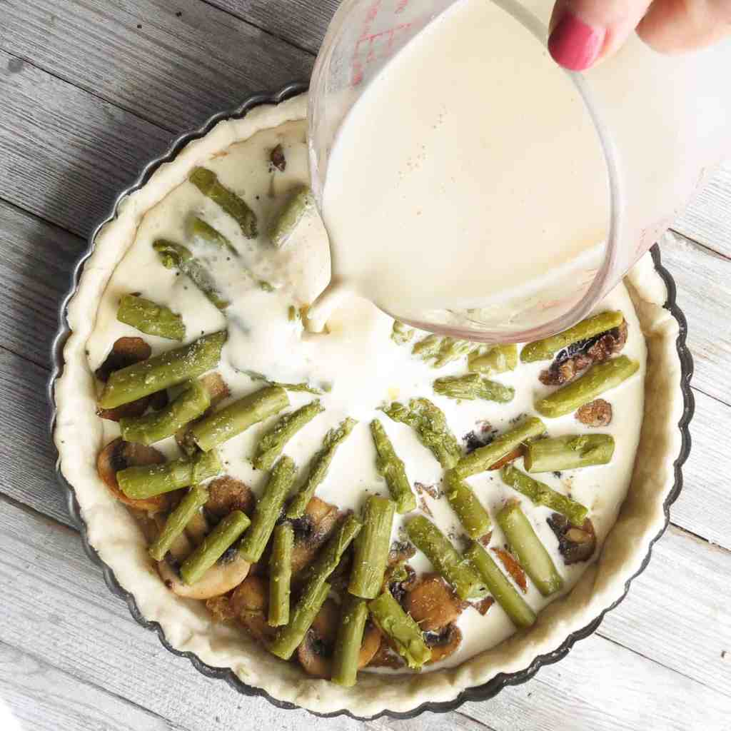 Pouring custard into a pie shell filled with asparagus and mushrooms for How To Make Quiche.