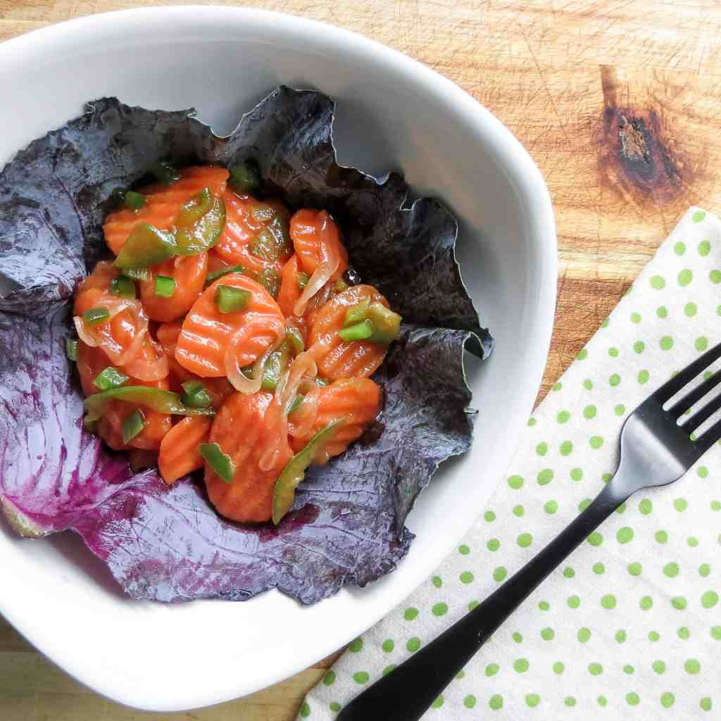 A white bowl lined with a leaf of purple cabbage filled with Copper Pennies Salad With Jalapeños next to a green polka-a-dot napkin and a black fork.