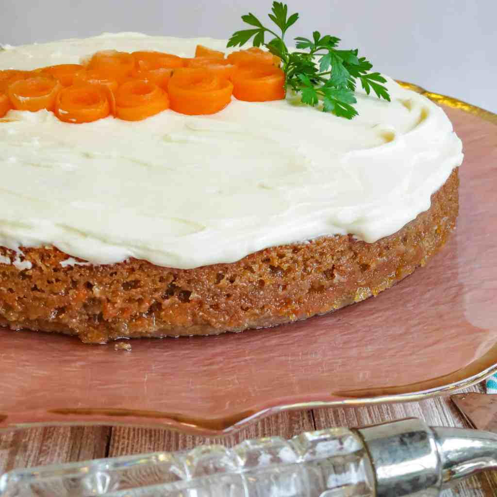 A Glazed Carrot Cake on a pink cake plate garnished with carrot curls and parsley leaves shaped to resemble a carrot.