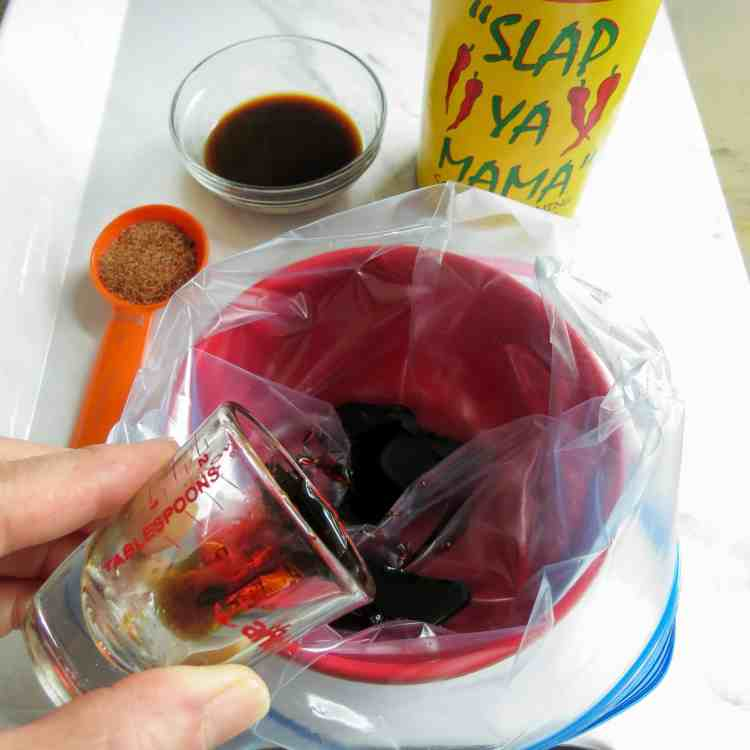 Sauce being poured into a ziplock bag in a red bowl with a can of Slap Ya Mama seasoning for Marinated Hot Dogs.