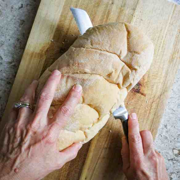 French Bread being sliced with a knife on a cutting board.