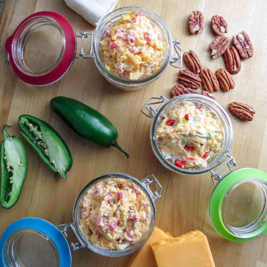 Three pimento cheeses in glass containers with jalapeño peppers, cheese, and pecans on a wooden board.