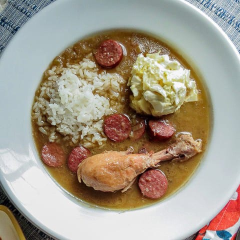 A white bowl of chicken and sausage gumbo with rice and a scoop of Plain Potato Salad in it.