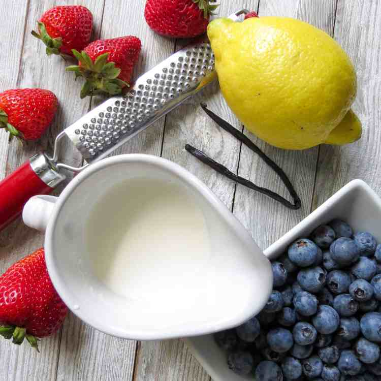 A small pitcher of cream on a wooden board with a zester , la lemon, a vanilla bean, a bowl of blue berries and strawberries scattered around.