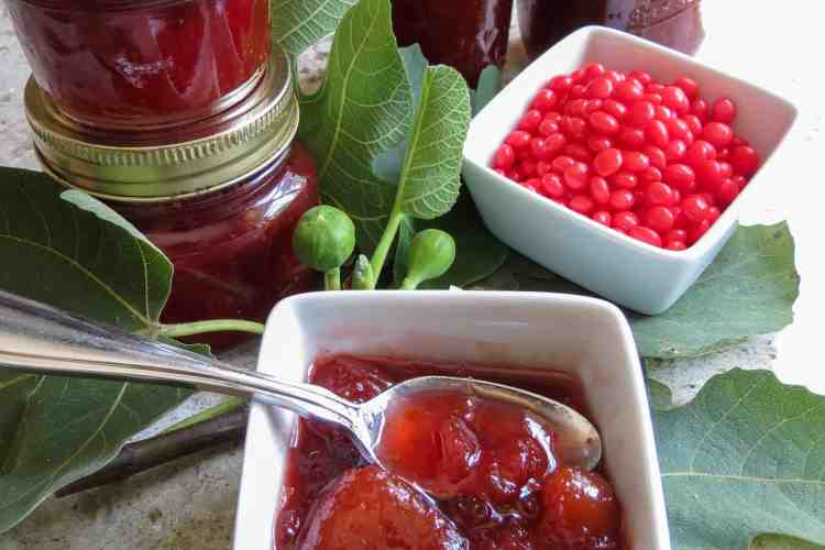 Bowls of fig jam and red hots with jars of fig jam.