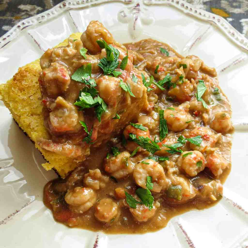 A dish of a square of cornbread topped with a crawfish stew.