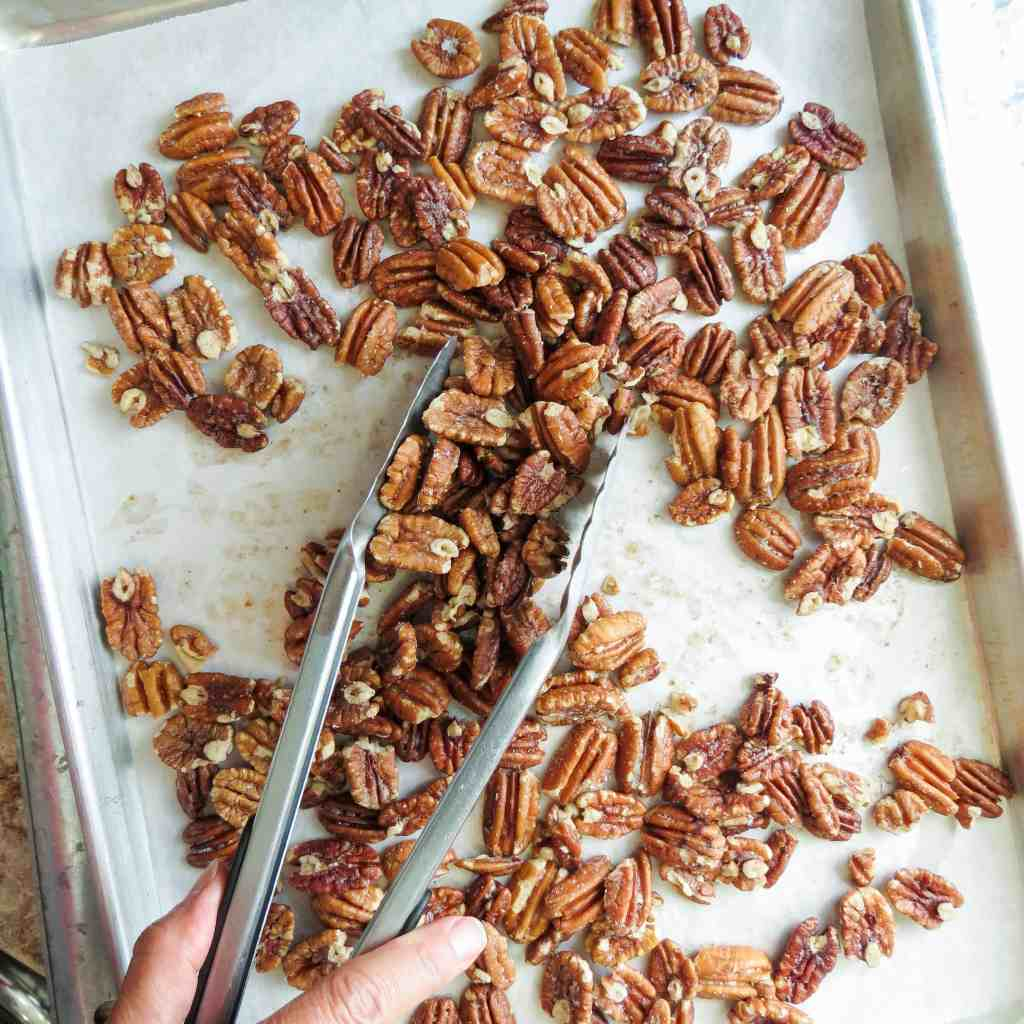 Pecans on a sheet pan lined with parchment paper tossed with long-handled tongs.