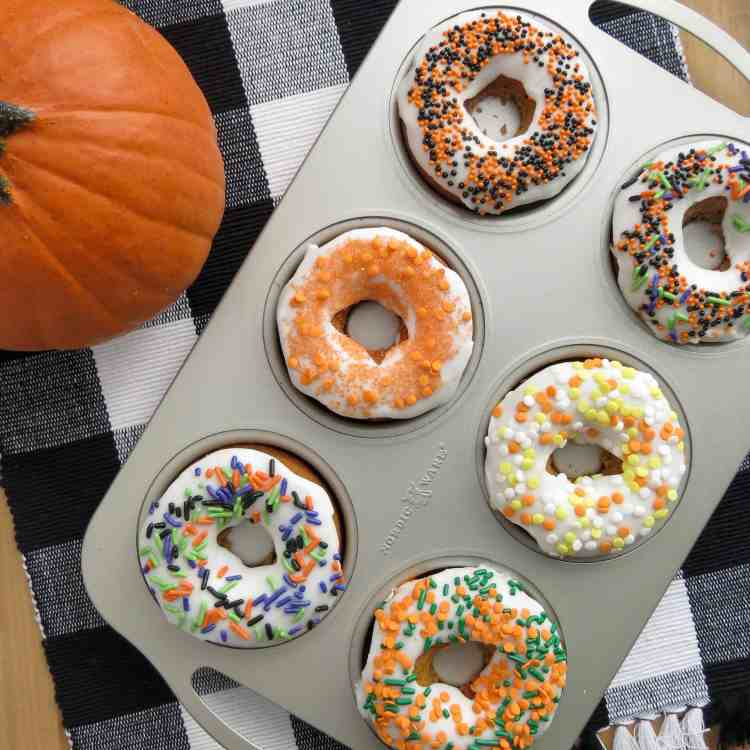 Iced and decorated donuts in a donut pan.