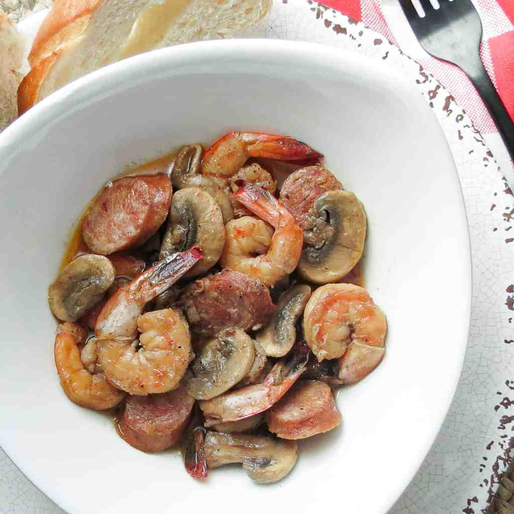 A bowl full of barbecue shrimp with mushrooms and smoked sausage.