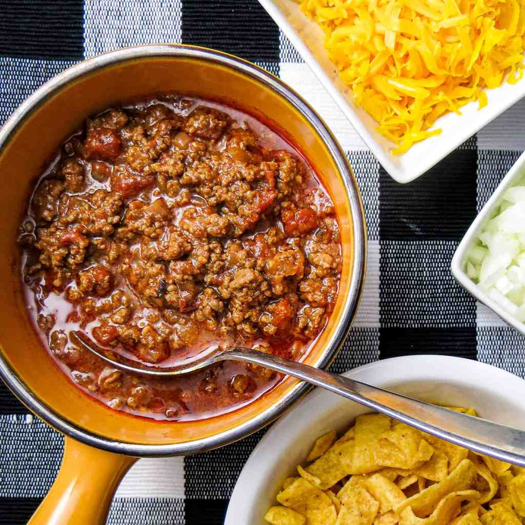 A pot of chili next to bowls of cheese, onions, and chips.