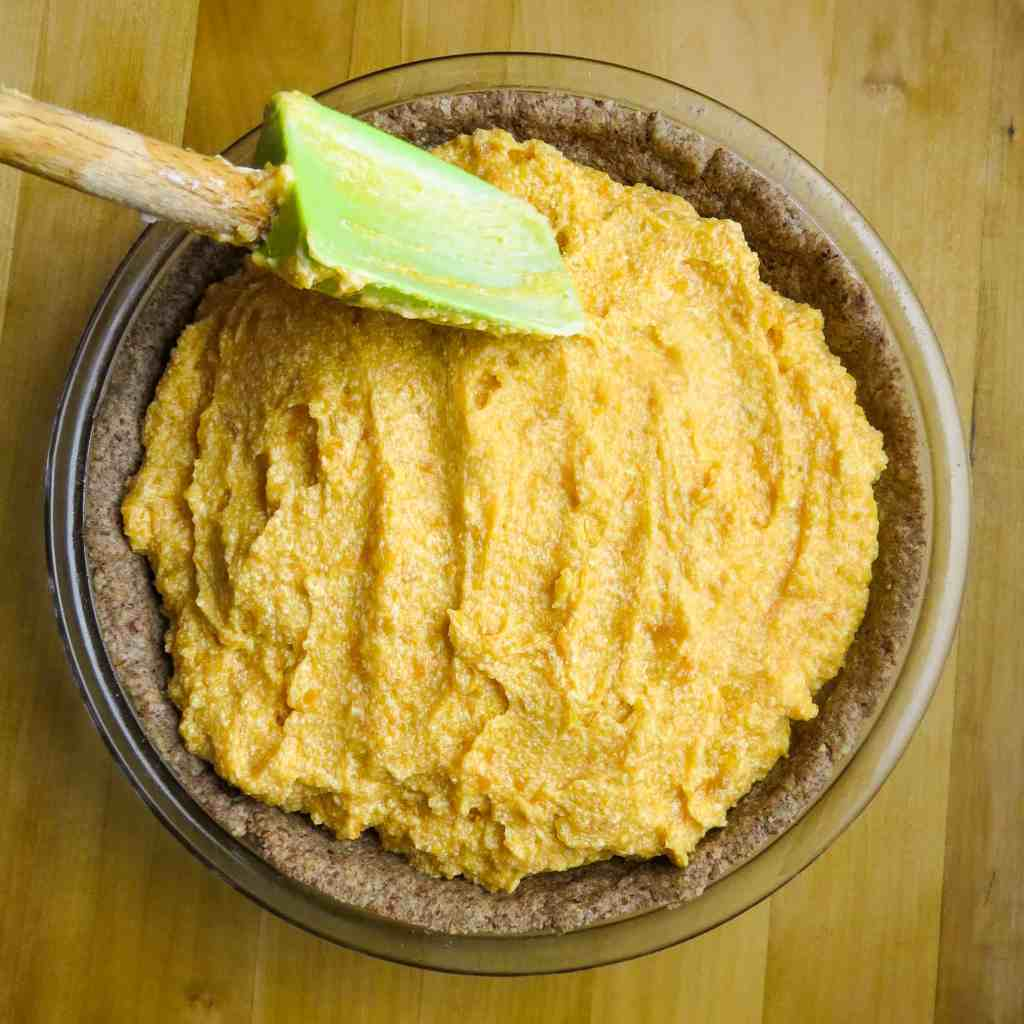 A spatula spreading pie fill into a pie crust.