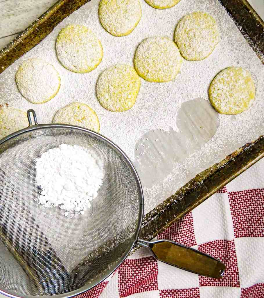 A cookie sheet of cooked cookies with powdered sugar.