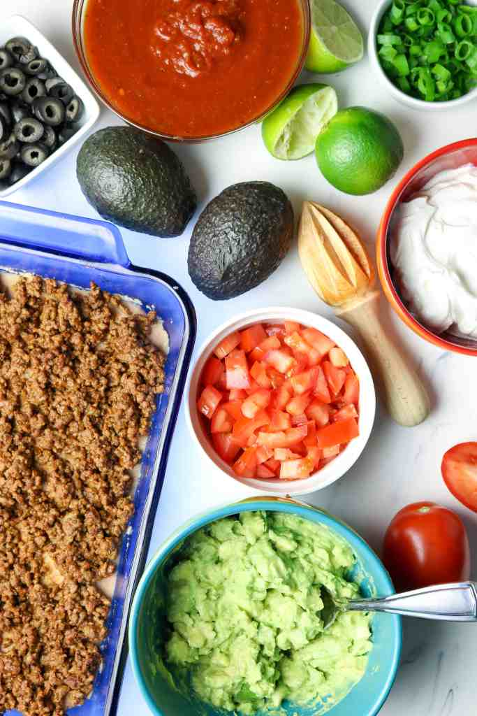 Ingredients of avocado, tomatoes, sour cream and taco meat for a baked dip.