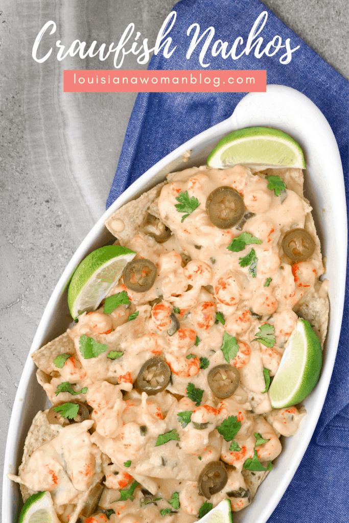 A dish of cheesy crawfish dip on top of tortilla chips with lime slices.