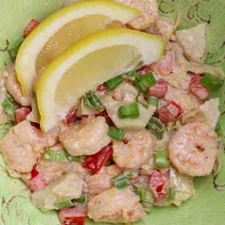 A serving of Shrimp Salad with 2 lemon slices.
