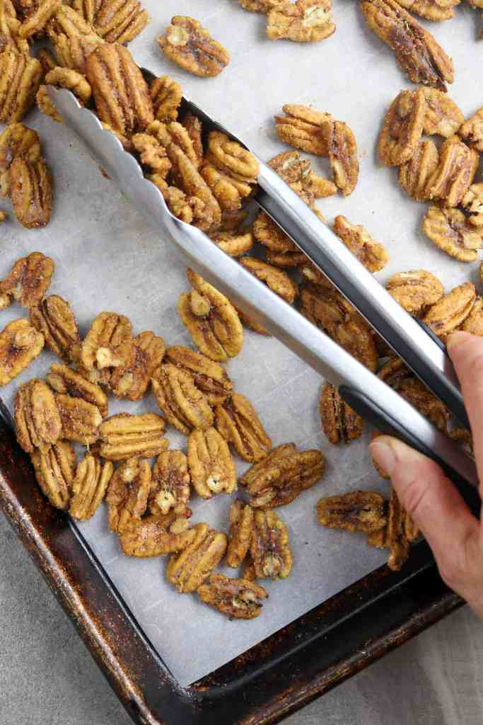 Tossing roasted pecans with tongs.