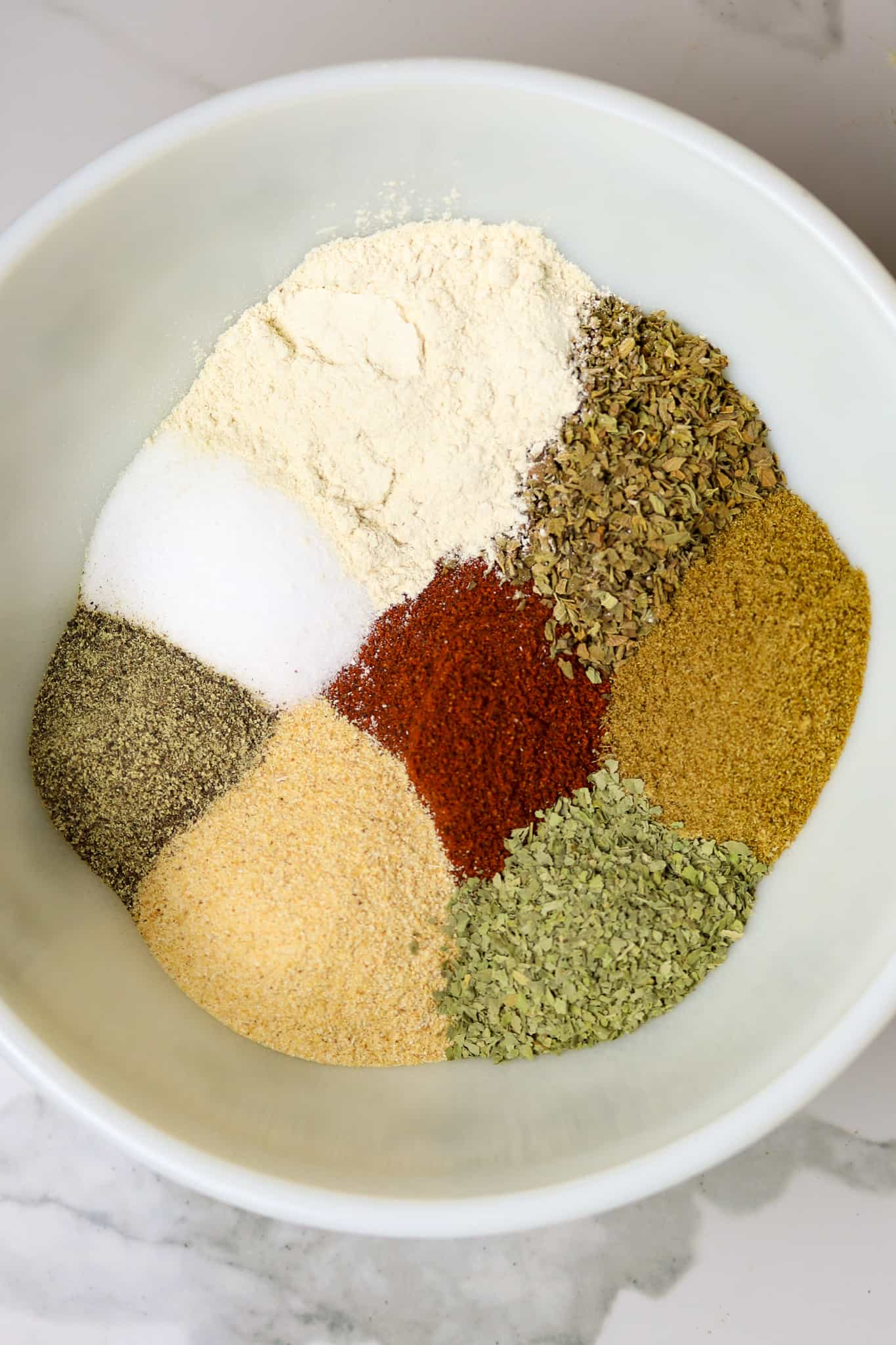 A bowl of several unmixed spices.