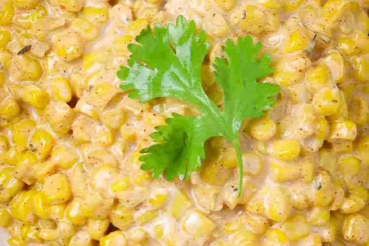 A bowl of Mexican Street Corn with a cilantro leaf as garnish.