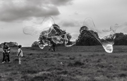 A black and white photo taken in a field. A large group of giant sized bubbles flying across the photo towards three boys.