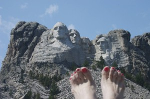 Lou Nell's bare feet w/pink toenails, Mt. Rushmore in background
