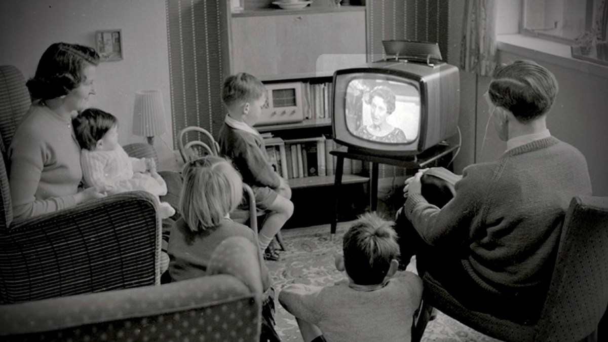 A stereotypical 1950s family sits around a television set.