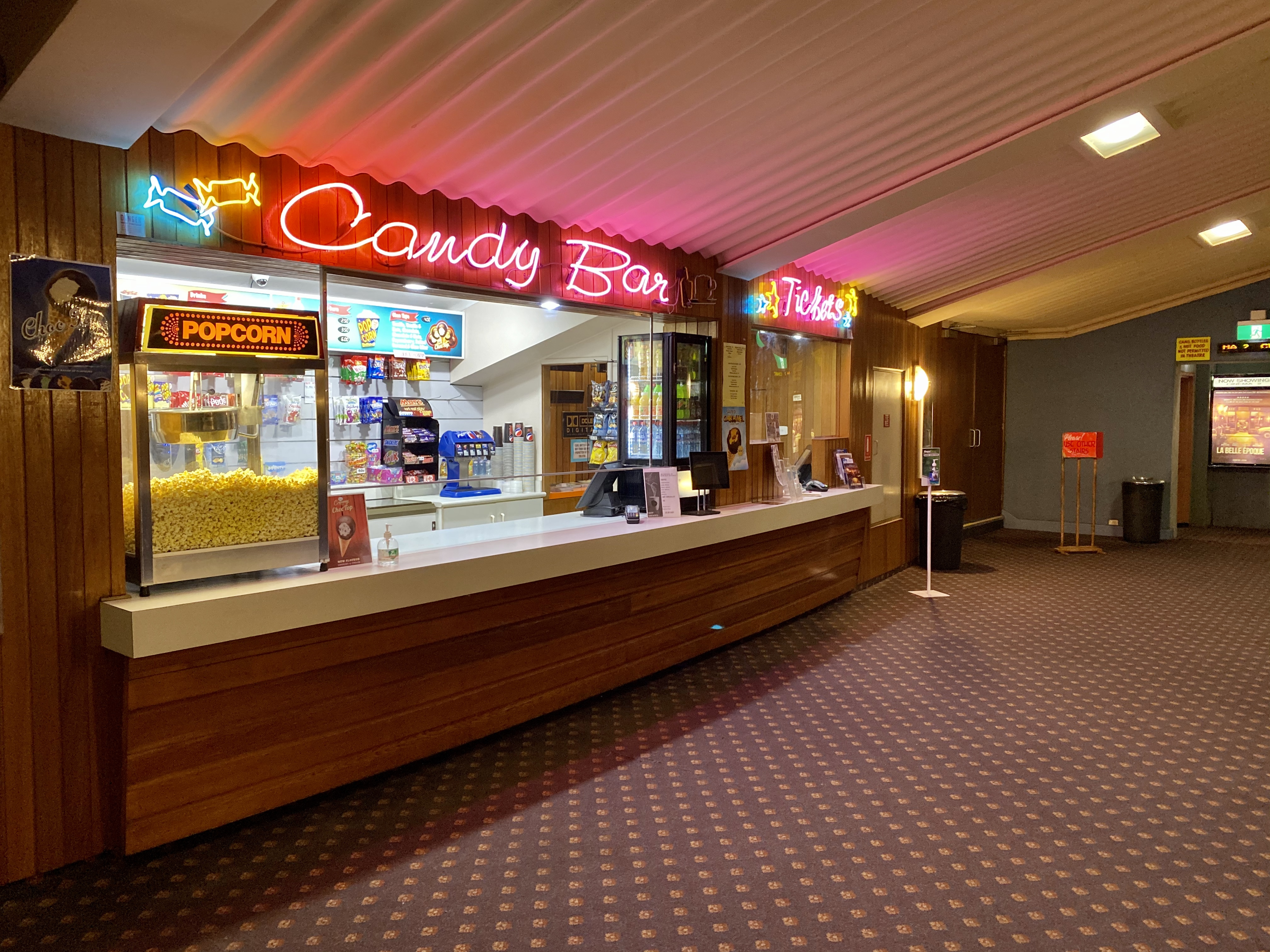 A counter with the sign candy bar and a popcorn machine under a sloping corrugated metal ceiling