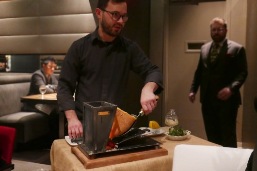 A raclette filled with hot coals melts the cheese table side.