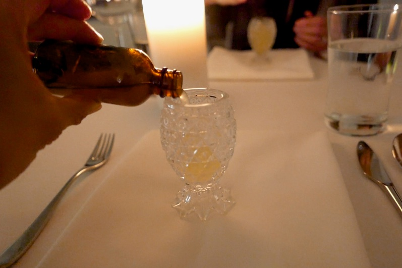 Pouring the bottle with the white sticker on the cap into our shot glass.