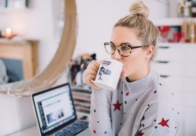 Female blogger drinking coffee at laptop