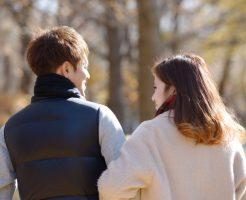 秋の公園でデートする若いカップル
