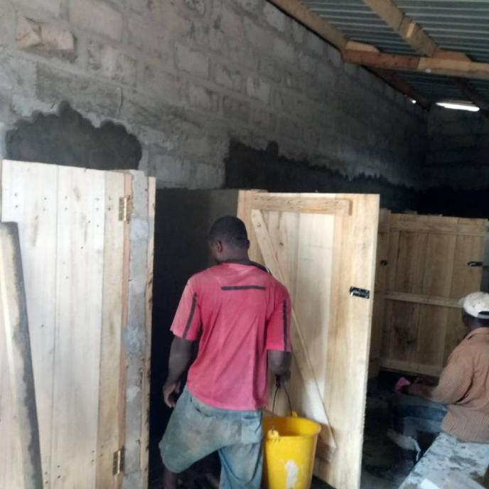 Walls in public washroom stalls being parged in Saltpond, Ghana project