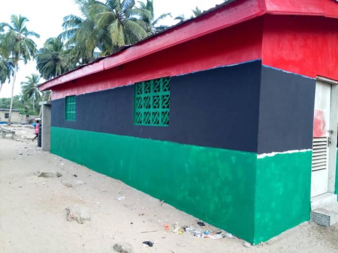 Green paint added to Love Africa Project public communal washroom building.